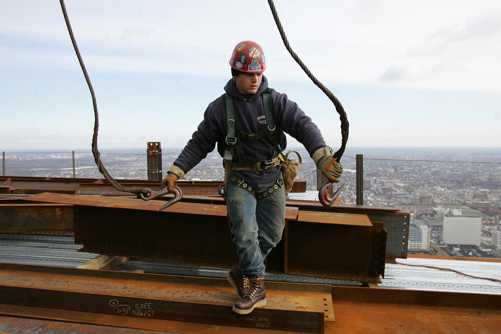 Irionworker prepares to connect a beam to the crane's  steel cable sorting hooks.