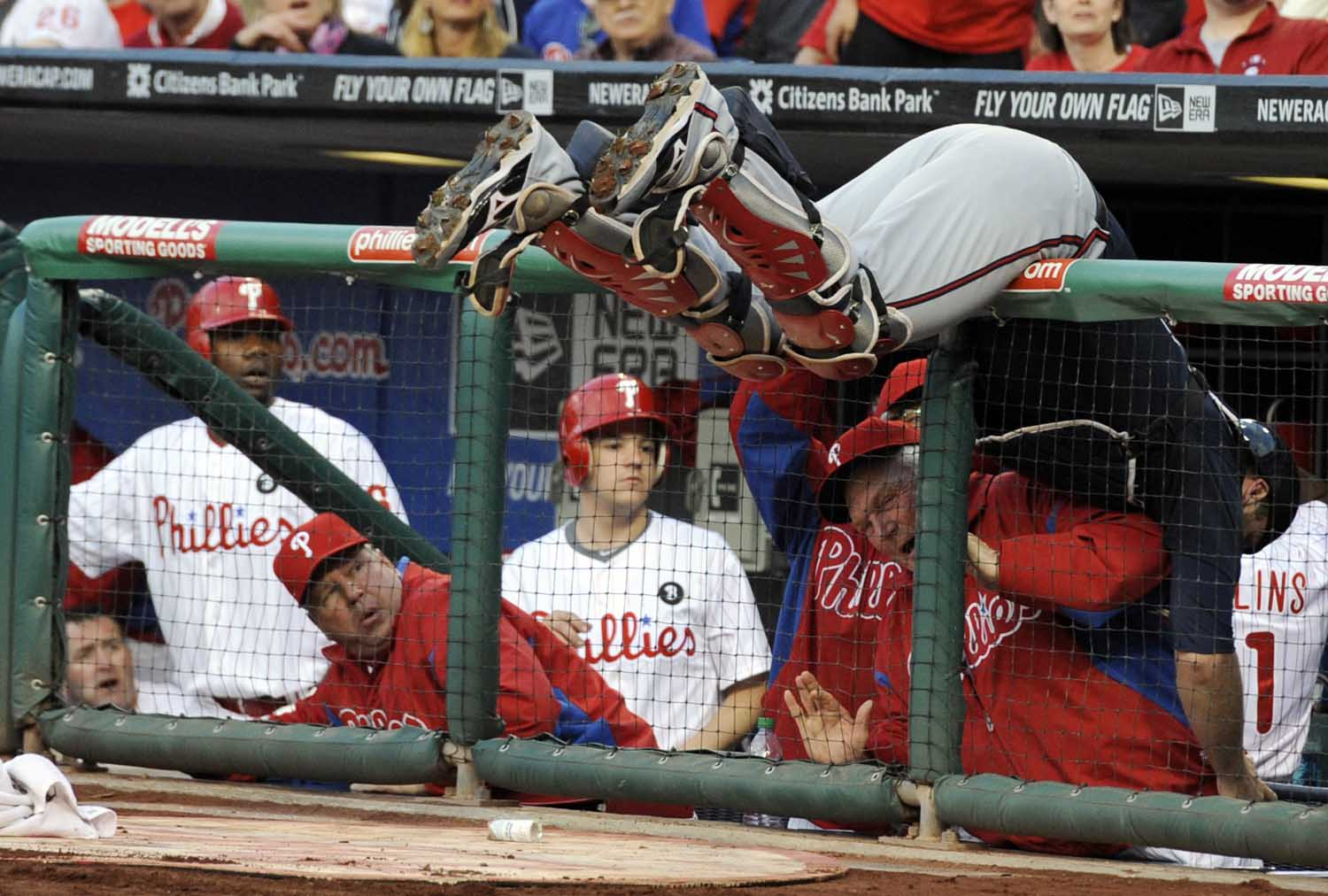 Atlanta Braves catcher Brian McCann falls over the dugout rail and over Philadelphia Phillies manager Charlie Manuel while trying to catch a foul ball hit by Shane Victorino during the first inning.