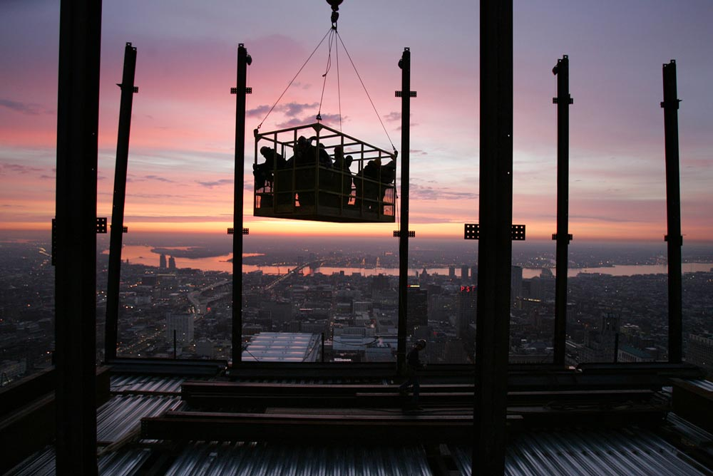 Ironworkers begin their day at sunrise as the crane hoists them in the man basket approximately 774 feet above street level to the 51st floor.