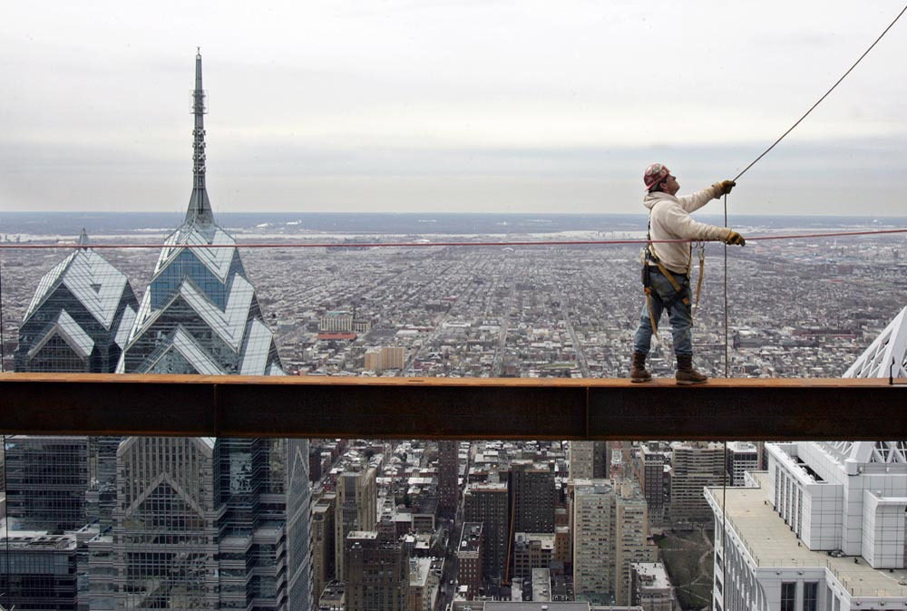 From a perimeter beam at approximately 842 feet above street level an ironworker releases the column pin on the top of a 34-foot column to free it from the crane's hook.
