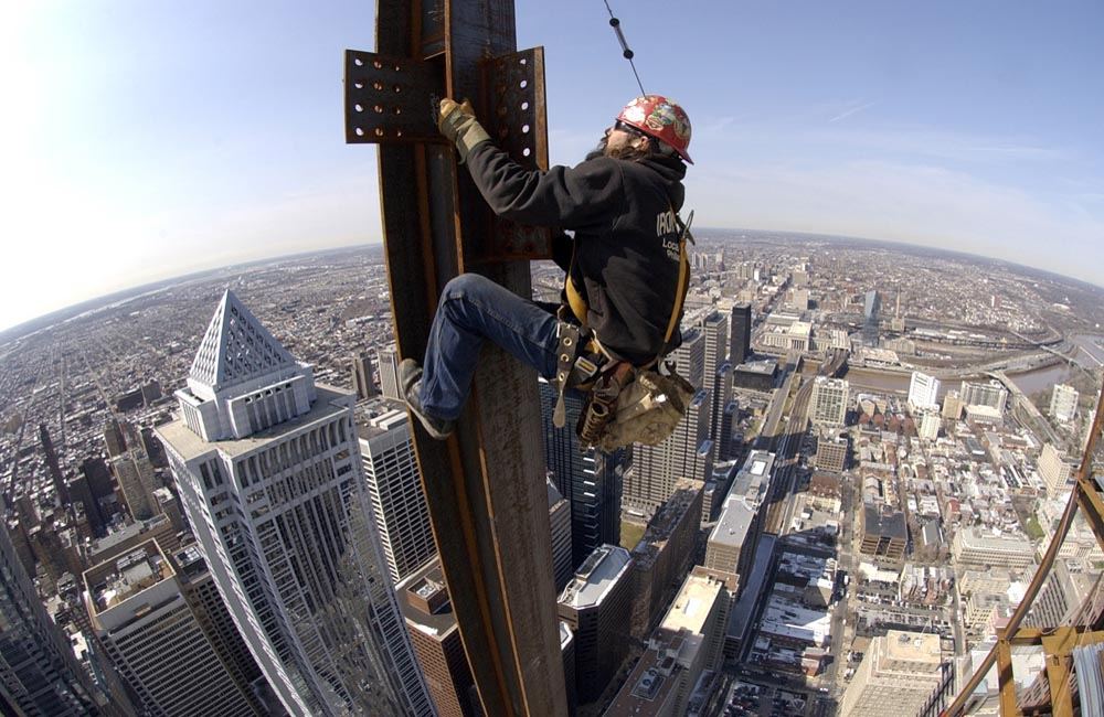 An ironworker climbs a column before connecting a perimeter beam to the 54th floor. He is working approximately 825 feet above street level.