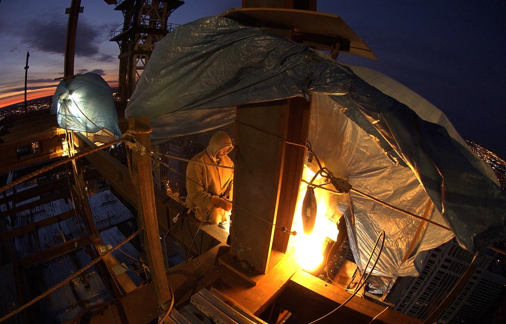 At sunrise under a blue tarp, an ironworker uses a torch to preheat a joint to 350 degrees on a 15-ton girder before welding. A small crew of welders took turns working 12-hour shifts for over 100 continuous hours to complete the job of welding the joints on two transfer girders.  Each girder came in two pieces, weighing 15 and 19.5 tons, which were erected on south side of the 55th floor of the Comcast Center. The joints on the two girders needed to remain at 350 degrees and kept dry through the duration of the welding.