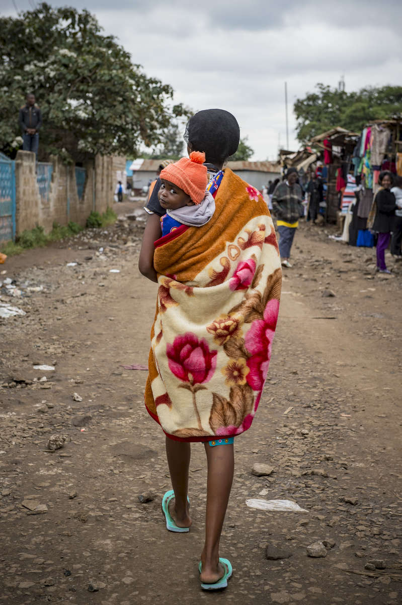 A woman carries her baby as she walks through the market in Dandora, Kenya.  (Photo by Barbara Johnston/University of Notre Dame)