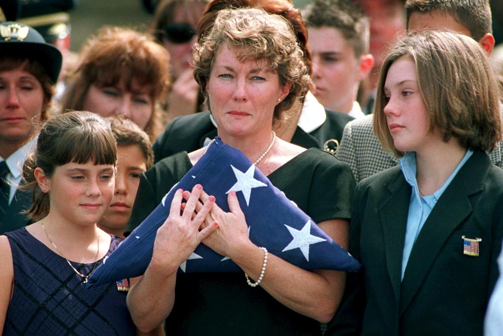 Funeral service for Victor Saracini, pilot of United Flight 175, which struck the World Trade Center. Widow Ellen Saracini holds the American flag as her daughters Brielle 10 (left) and Kirsten 13 stand by her side.