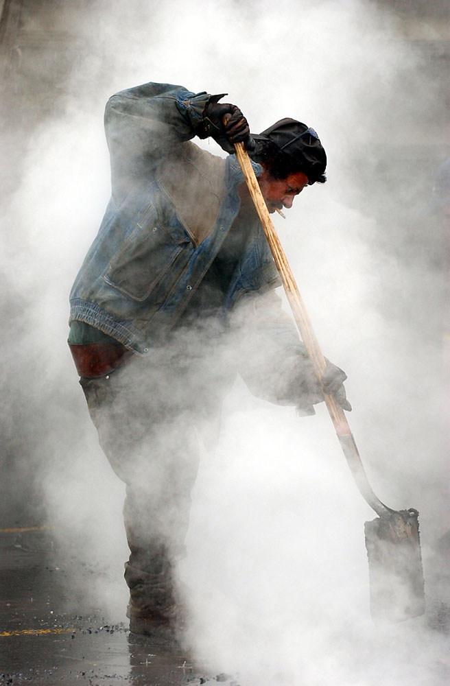 Steam rises as Richardo Pacheco, 50, spreads fresh asphalt in the parking lot at the West Goshen Shopping Center in West Chester, Pennsylvania. Pacheco was working with a crew who were paving electrical trenches for parking lot lights.