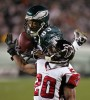 Eagles wide receiver Greg Lewis makes a 27-yard pass reception as Atlanta Falcons cornerback Allen Rossum defends during second quarter.