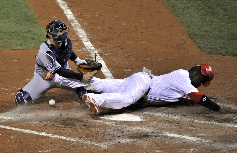 Philadelphia Phillies first baseman Ryan Howard (right) scores past New York Yankees catcher Jorge Posada during the fourth inning of game four of the 2009 World Series at Citizens Bank Park.