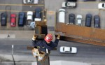 A third-year apprentice, guides a steel beam into place on the 43rd floor. He is tied off on a column, approximately 638 feet above 18th Street, where a motorist passes.
