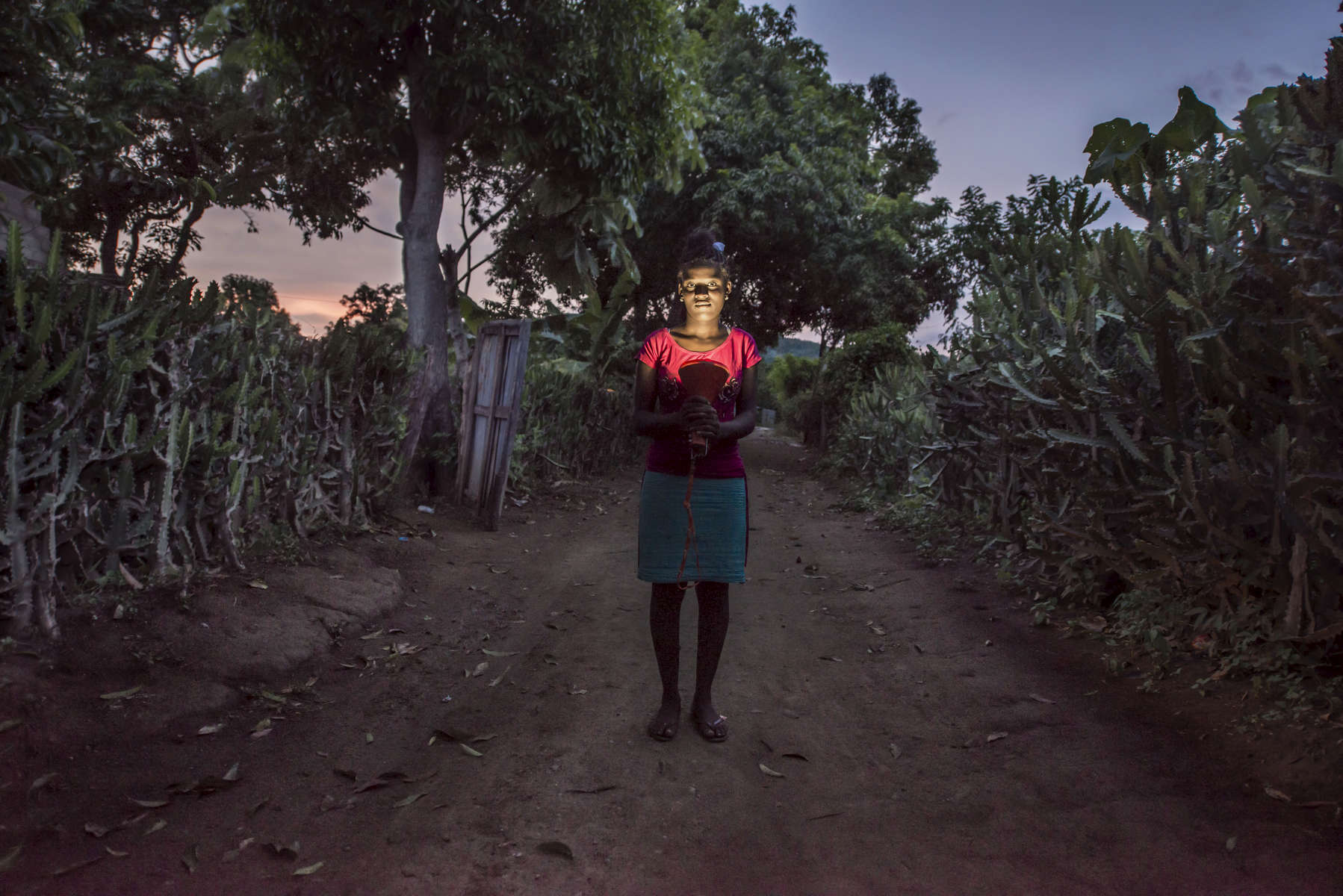 Guivelorna Laguerre holds a solar lantern from Let's Share the Sun Foundation in Fontaine, Haiti