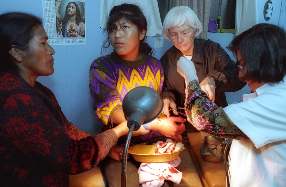 Christ the Worker parish operates a clinic for the poor, where Sister Patricia assists Dr. Fatima Luisa Pastor Aramayo (right) in stitching a bad wound in Lourdes Lugue Hayasi's hand. On left, Lourdes' mother, Filberta Hayasi de Luque also helps.