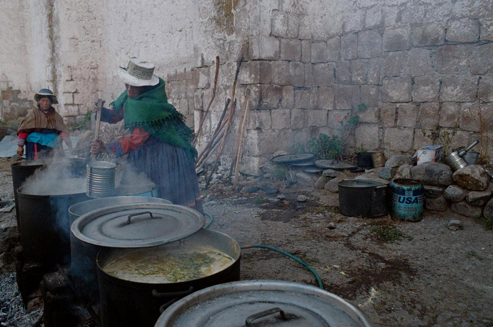 Improving nutrition is one of Sister Patricia's efforts. In the village of Yanque, Quechua women cook a nutritionally balanced soup at a community kitchen initiated by the Medical Mission Sisters. Villagers bring their own containers to take soup home.