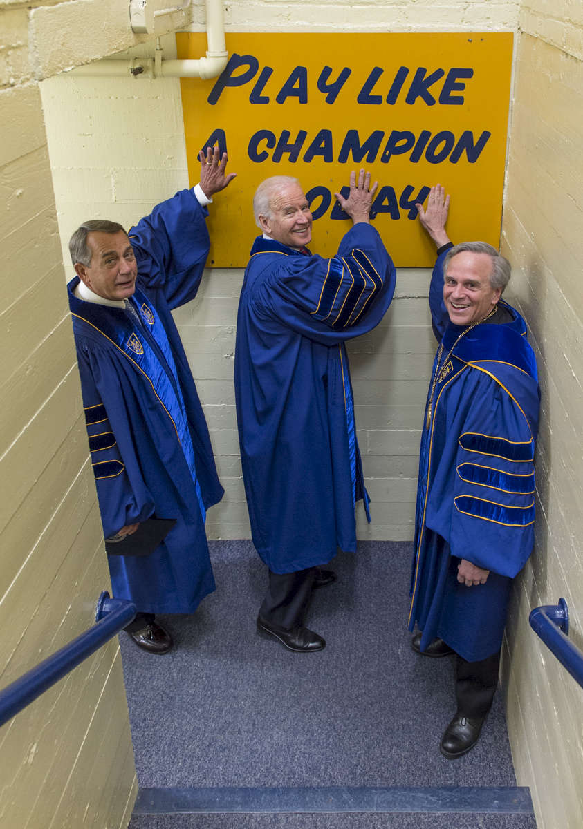 University of Notre Dame president Rev. John Jenkins, C.S.C. and Laetare Medal recipients, John Boehner, former Speaker of the House and Vice President Joe Biden, touch the Play Like A Champion Today sign on their way out of the locker room for the 2016 Commencement Ceremony at Notre Dame Stadium.