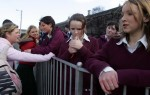 Catholic students wait at a bus stop in Limerick, Ireland