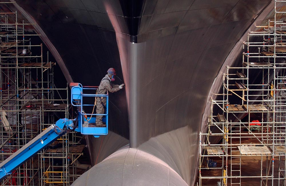 On a cherry picker, shipyard worker Dario Pena does grinding work on the bow of a container ship before it is painted in a dry dock at the Kvaerner Philadelphia Shipyard on March 16, 2005.