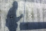 An ironworkers' shadow is cast against the building's cement core as he guides a beam.