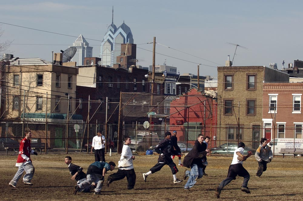 Young men play football on a sunny Sunday afternoon at Capitolo Playground, Ninth and Federal Streets.