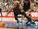 Chicago Bulls' Dennis Rodman dives for the ball as Philadelphia 76ers' Aaron McKie (right) defends on the play during first quarter action.