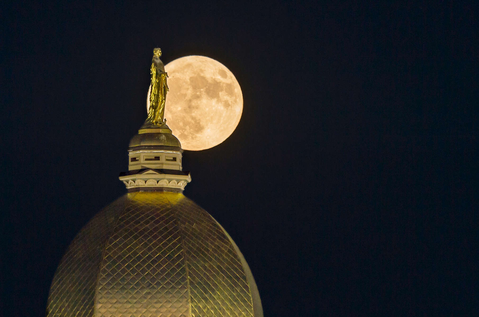 A super moon rises behind the  Golden Dome.