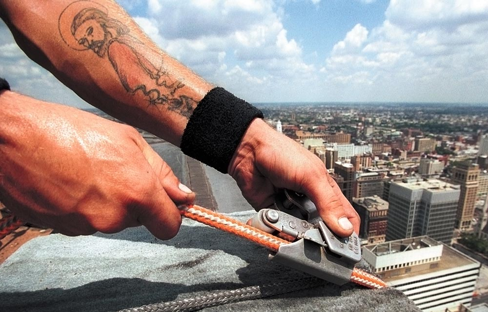 Billy Moncrief adjusts safety rope on the roof of the PNC Bank Center.