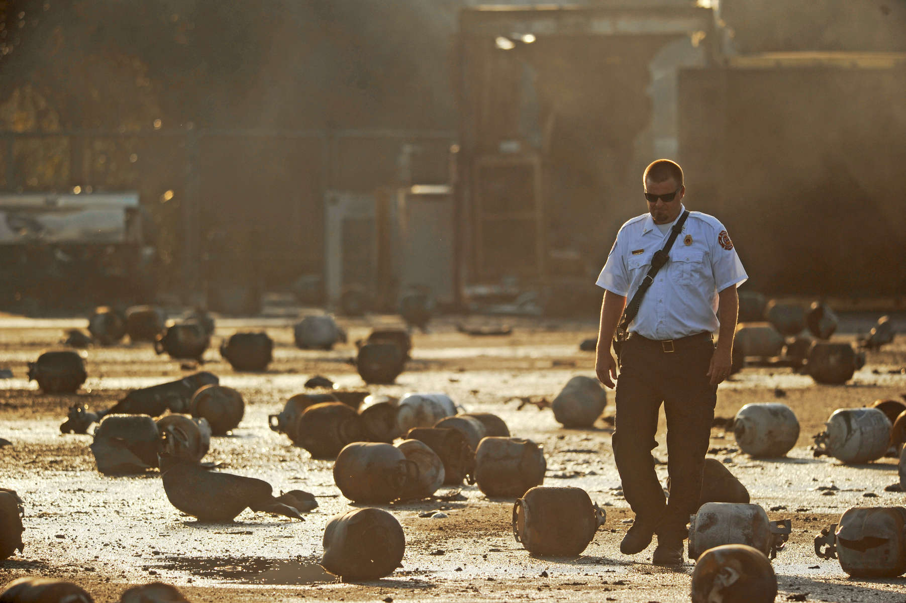 Tavares Fire Battalion Chief Jeff Hosterman walks through the remains of exploded propane cylinders litter the storage yard of a propane plant following massive explosions overnight in the plant's yard on Tuesday, July 30, 2013 in Tavares Fla. Eight people were transported to local hospitals according to Lt. John Herrell of the Lake County Sheriff's Office. No one was killed in the blasts, said Herrell.