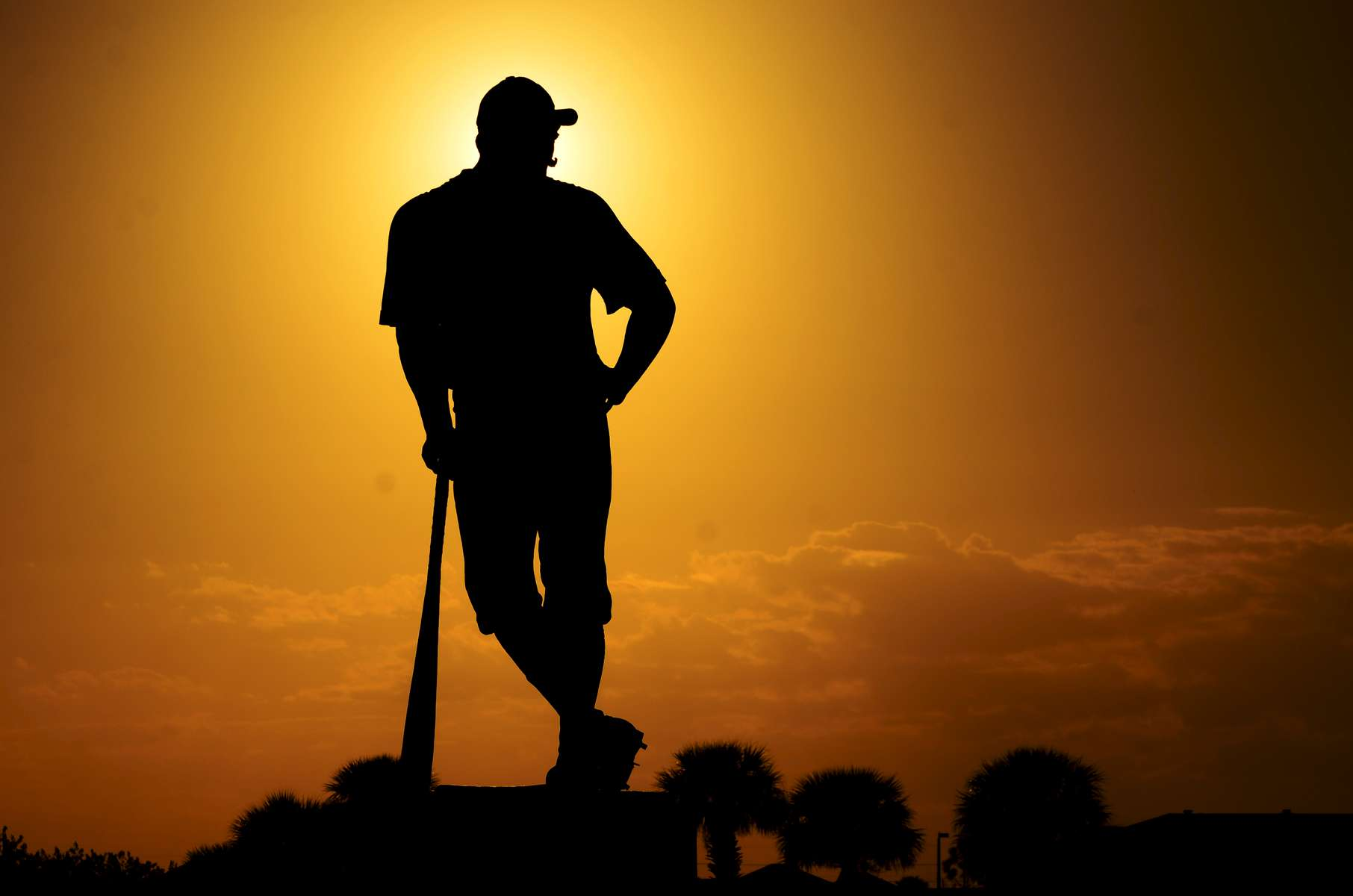 A statue of a baseball player is silhouetted outside Space Coast Stadium on Sunday, March 2, 2014 in Melbourne, Fla.
