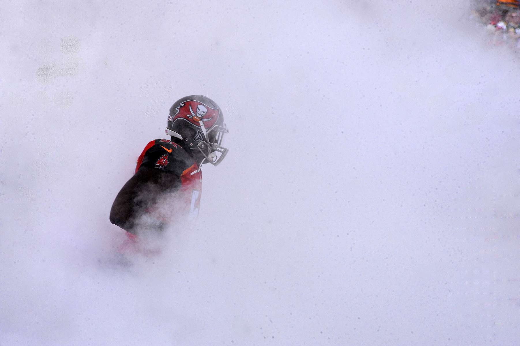 Tampa Bay Buccaneers linebacker Jason Williams (52) runs through pre game smoke as the Green Bay Packers beat the Buccaneers 20-3 at Raymond James Stadium on Sunday, December 21, 2014 in Tampa, Fla.
