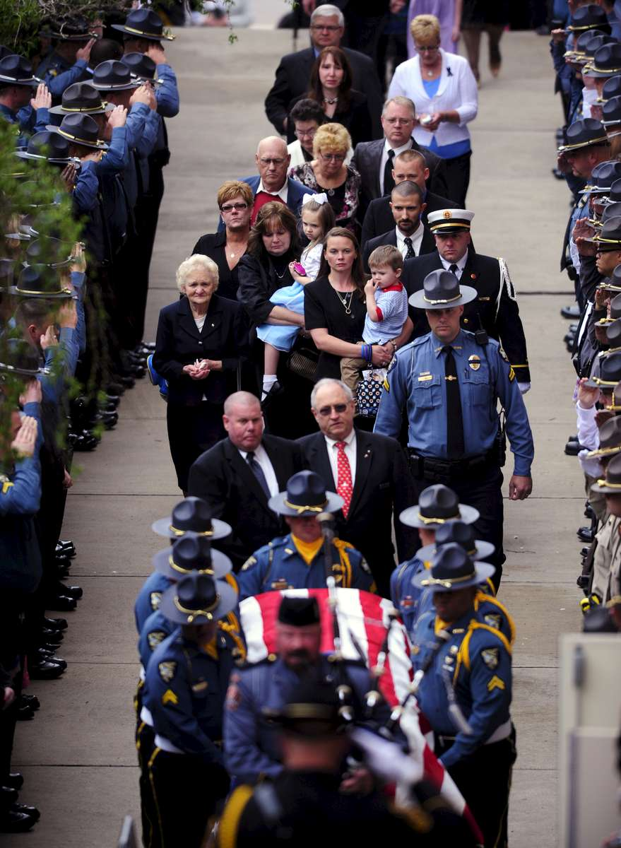 Melissa Christian, center, holds her two-year-old son Wyatt as they follow the casket of her husband Athens-Clarke Senior Police Officer Elmer {quote}Buddy{quote} Christian during his funeral at The Classic Center on Sunday, March 27, 2011 in Athens, Ga. Christian was murdered Tuesday by 33-year-old Jamie Hood who shot both Christian and fellow Senior Patrol Officer Tony Howard during a traffic stop.  Hood surrendered to police Friday after an extensive manhunt.