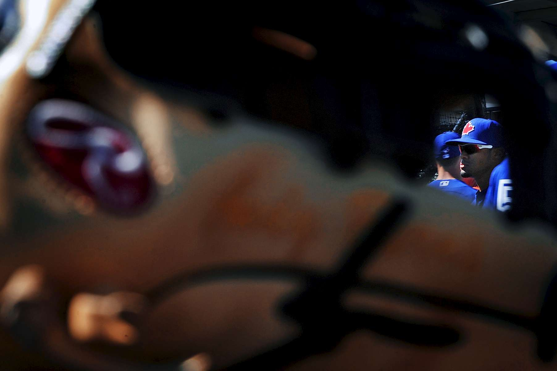 Toronto Blue Jays left fielder Melky Cabrera (53) is seen through a baseball glove warms up before facing the Baltimore Orioles in a spring training exhibition game at Ed Smith Stadium on Saturday, March 1, 2014 in Sarasota, Fla.