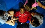 Issac Wyatt, center, is helped with situps by students Zoe Katz, left, Crockett Floyd, top, and Paige Maddox, right, during an adaptive physical education class at Malcom Bridge Middle School on Thursday, November 18, 2010 in Bogart, Ga.  Eighth grade students help disabled students exercise during the three day-a-week program.