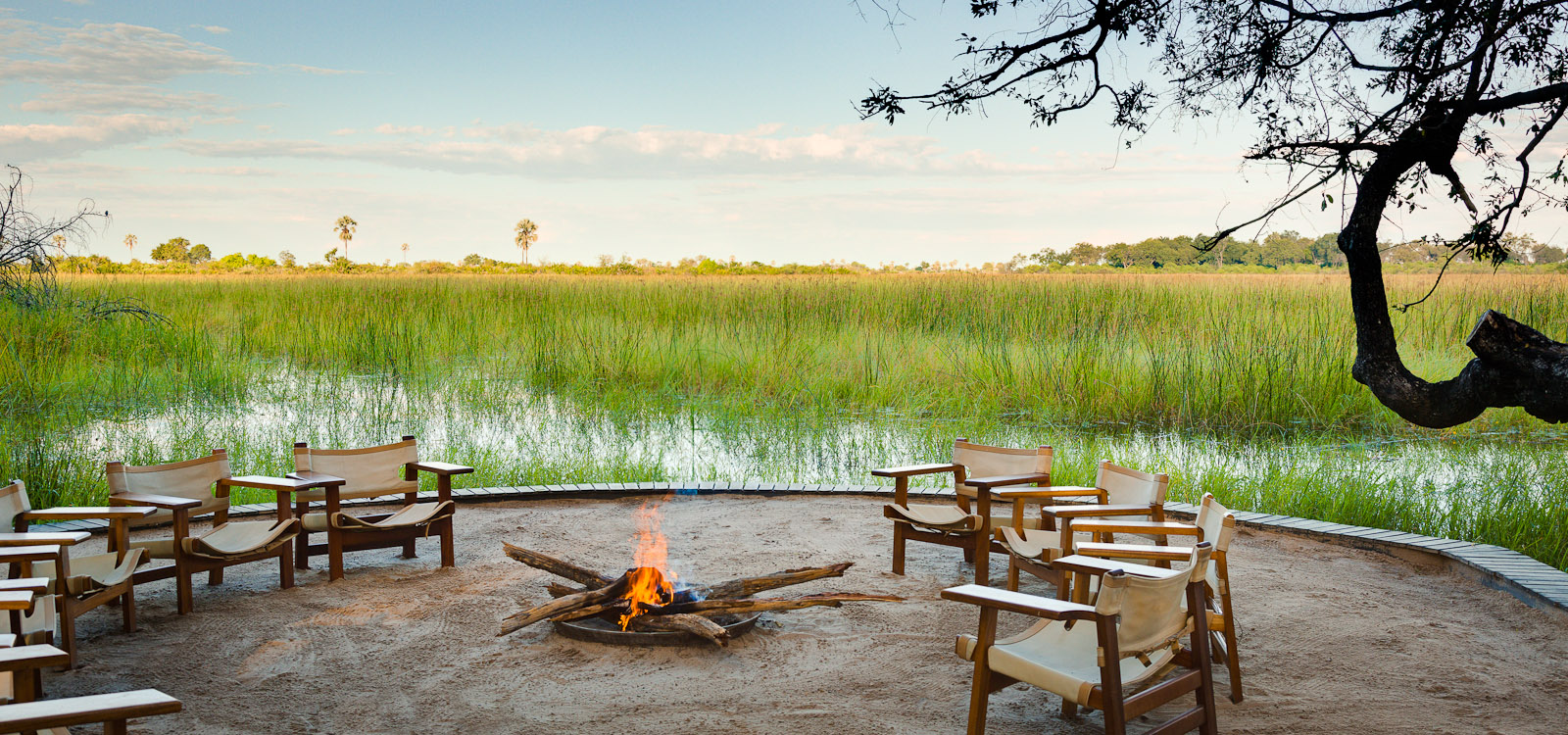 Fire pit at Abu Camp. Early morning breakfasts, high tea, sundowners, and dinner can be enjoyed in this open air setting. Abu Camp is a Wilderness Safari's Collection Camp in the Okavango Delta, Botswana. Photo © 2012 Jay Graham, all rights reserved