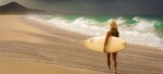 Liz walking with her surf board on the beach in front of Rancho Pescadero south of Todos Santos, Baja, Mexico. Rancho Pescadero is featured in Sunset Magazines In the mood for pampering.