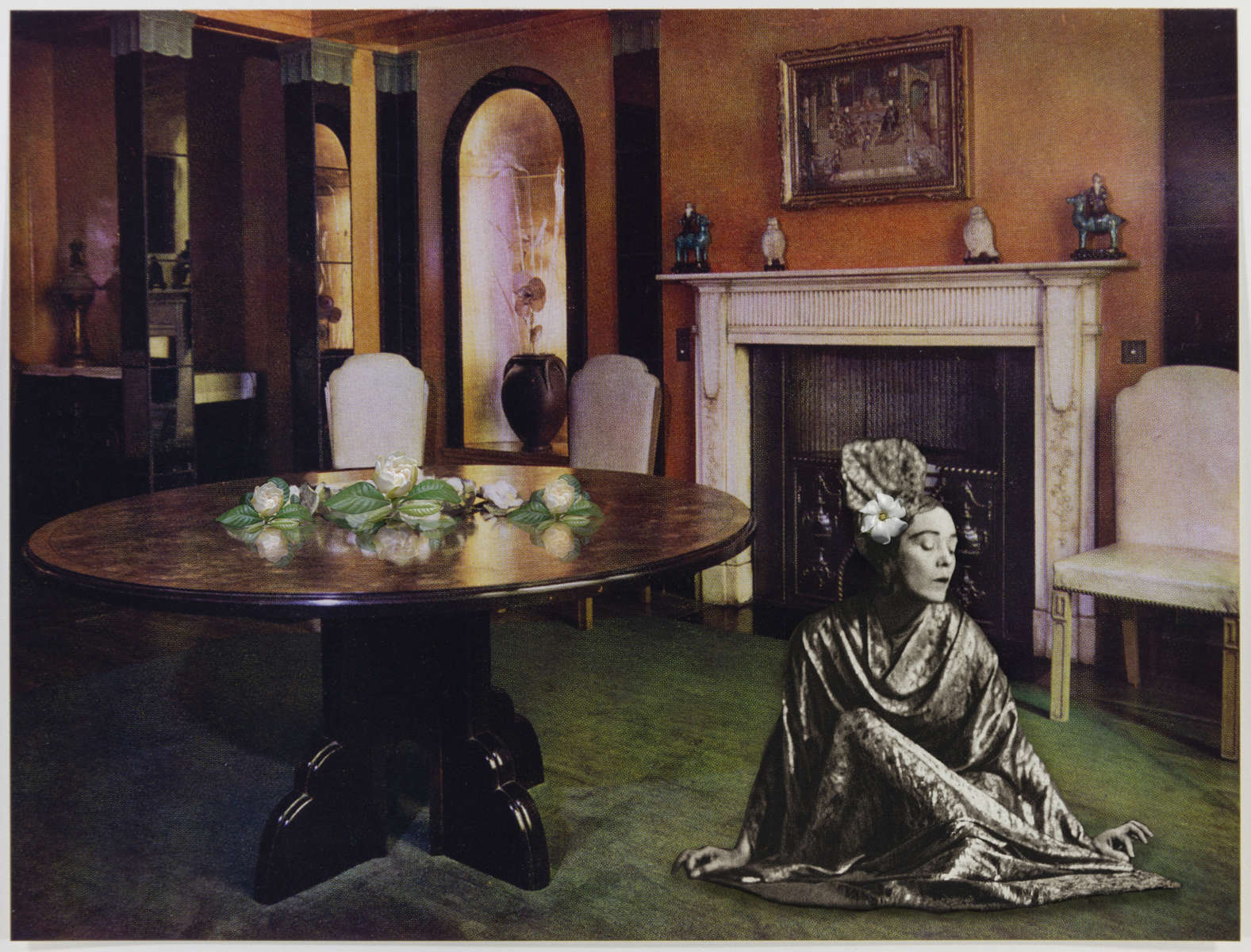 This dining room, designed by R. W. Symonds and Robert Lutens for the Baroness Ravensdale, shows a scheme devised as a setting for its owner's collection of Chinese jade and lacquer. The walls and ceiling are painted a Venetian red and decorated with pilasters carried out in black mirror glass with fluted caps and bases in Pompeian green. Black mirror glass also forms the architraves, which, lined with lacquered gold leaf, decorate the niches on each side of the fireplace. Gardenias rest gently on the table and in Mary Wigman's hair. (2018)