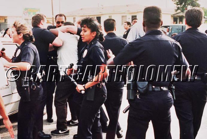 Immediately following the Rodney King verdict on April 29,1992 the LAPD confronts a rock and bottle throwing crowd  looting a liquor store at the corner of Florence and Normandie.