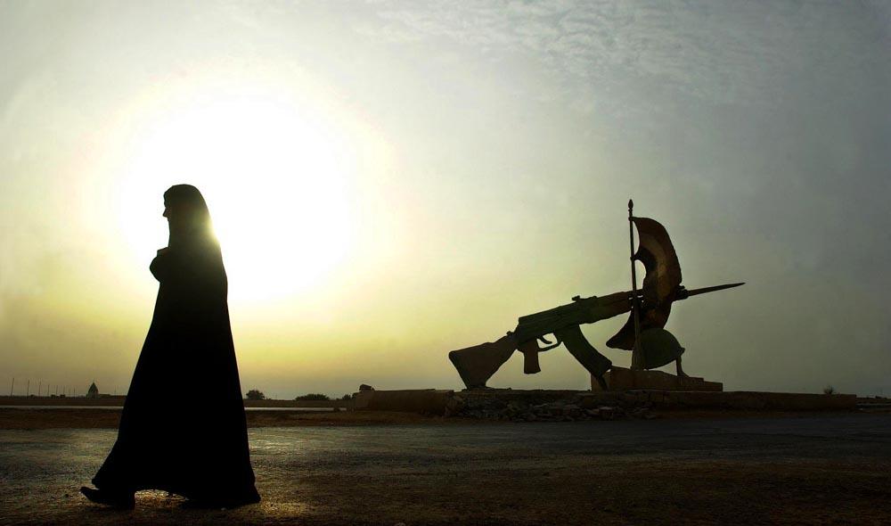 An Iraqi woman in Ad Diwaniyah walks past a former Iraqi military complex in April, 2003.