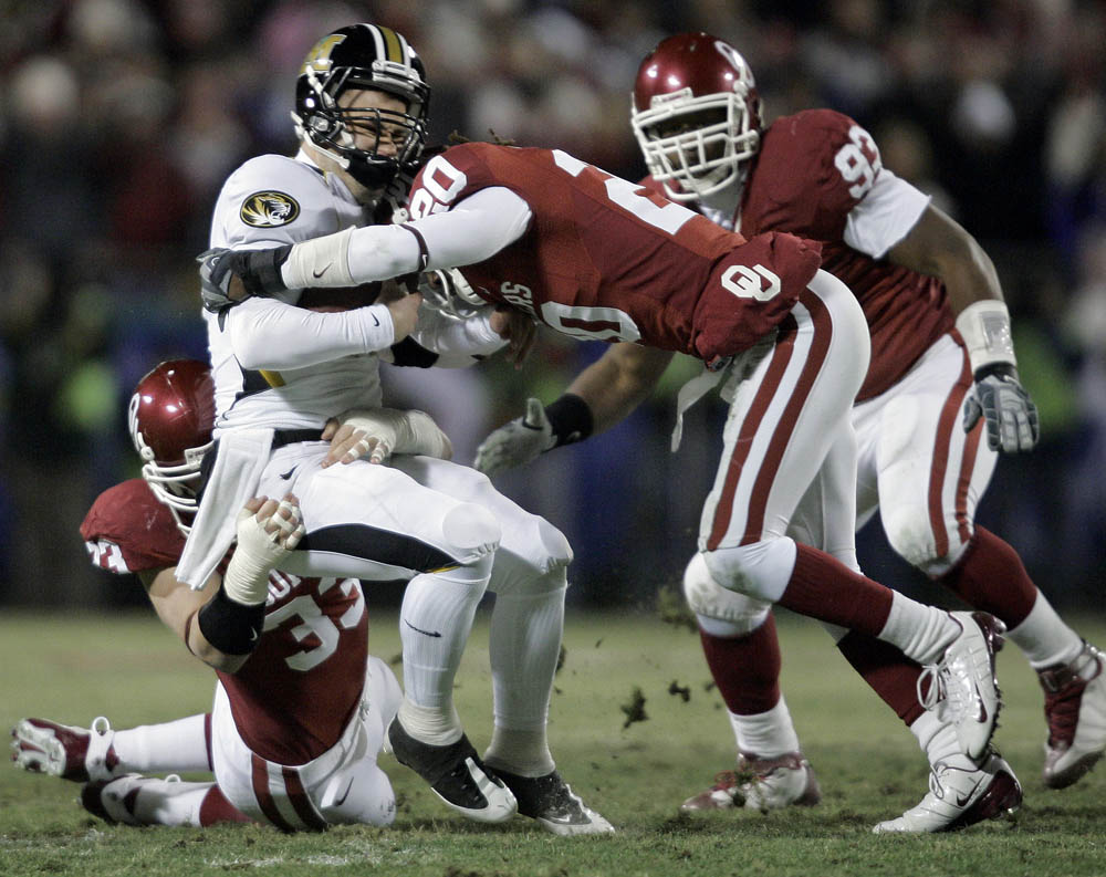 Missouri QB Chase Daniel gerts tackled by Oklahoma teammates Auston English (left) and Quinton Carter (right) during the Big 12 Championship.