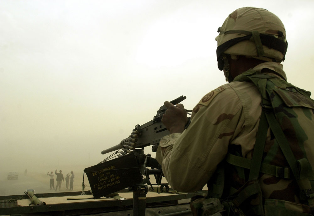 Iraqis wave to soldiers of the 82nd Airborne during a sandstorm en route to Baghdad.