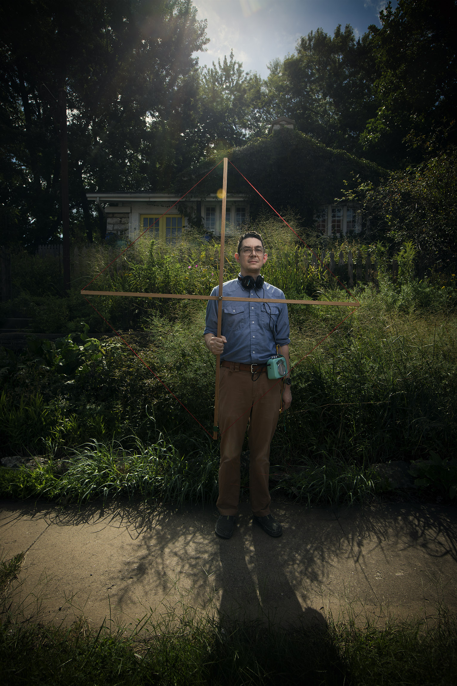 "Portrait of Shawn Hansen in front of his Rosedale home that was landscaped by Barbara McReery with native perenials. Hansen holds onto his antenenna called ""very low frequency"" radio antenna which can listen to sounds of the earth's electro magnetic shield."