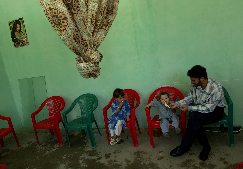 An Afghan father shares ice cream with his two children from a ice cream parlor in Kabul, Afghanistan.