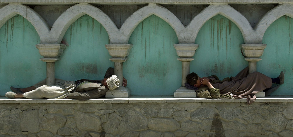 Two Afghan men take a nap at the Hagi Yaqub crossroad in the Shahar-e-naw district of Kabul, Afghanistan.