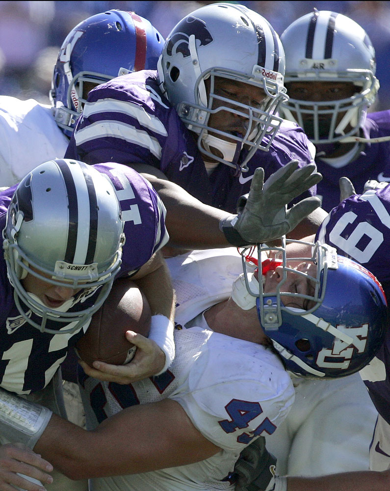 Kevin Kane (45) of Kansas gets a face full from Kansas State lineman Greg Wafford (top) while trying to tackle Kansas State QB Allan Evridge.