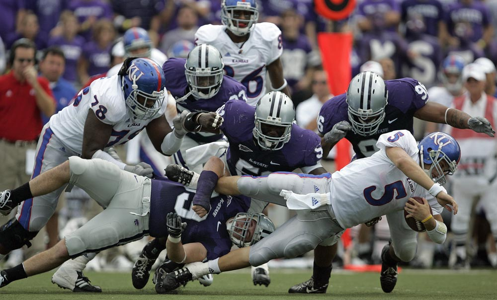 Kansas quarterback Todd Reesing (5) tries to escape from John Houlik (bottom left) and the rest of The Kansas State defense.