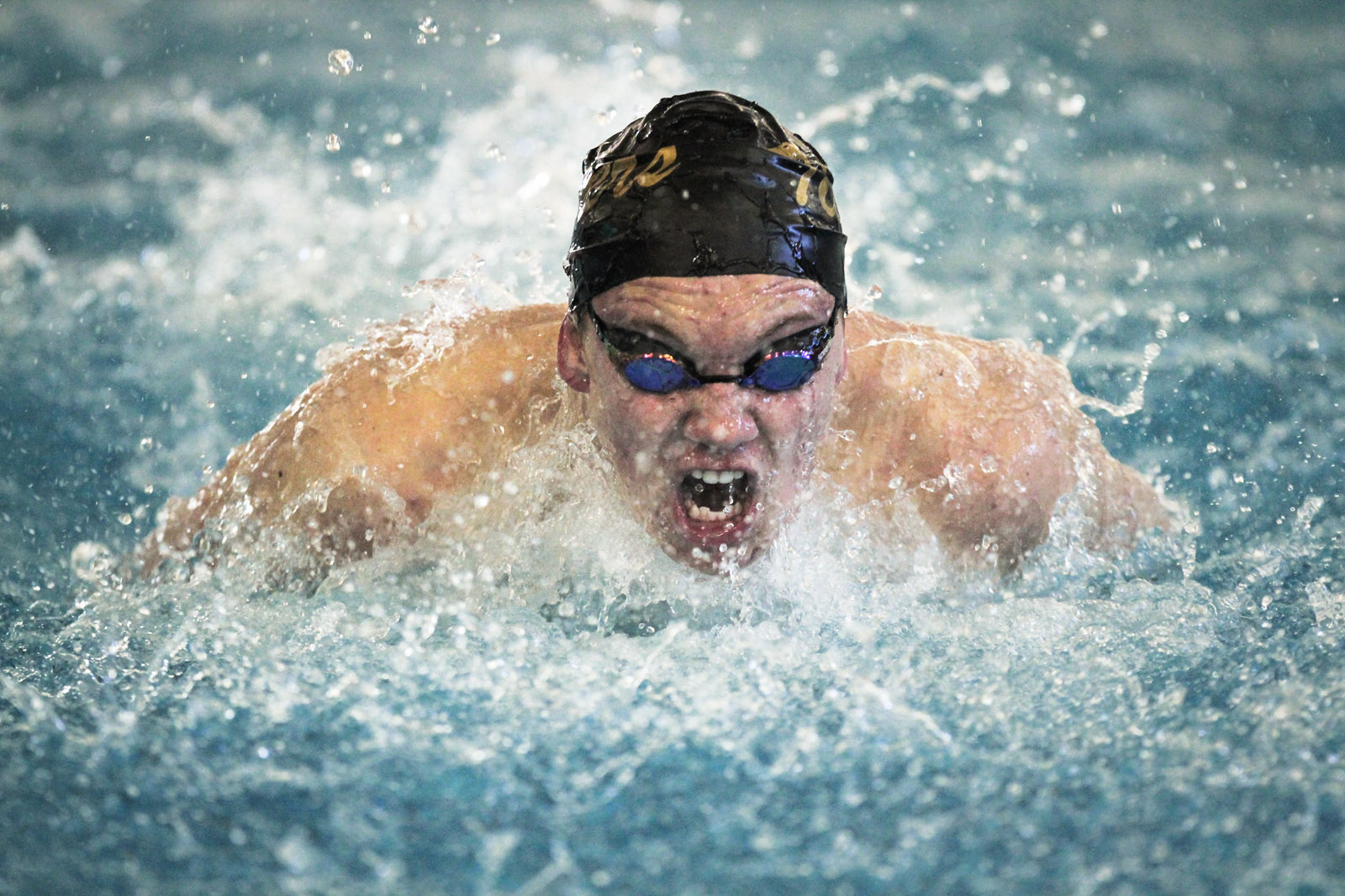 Chris Hearl of Blue Valley High School competes in the 100 yard butterfly.