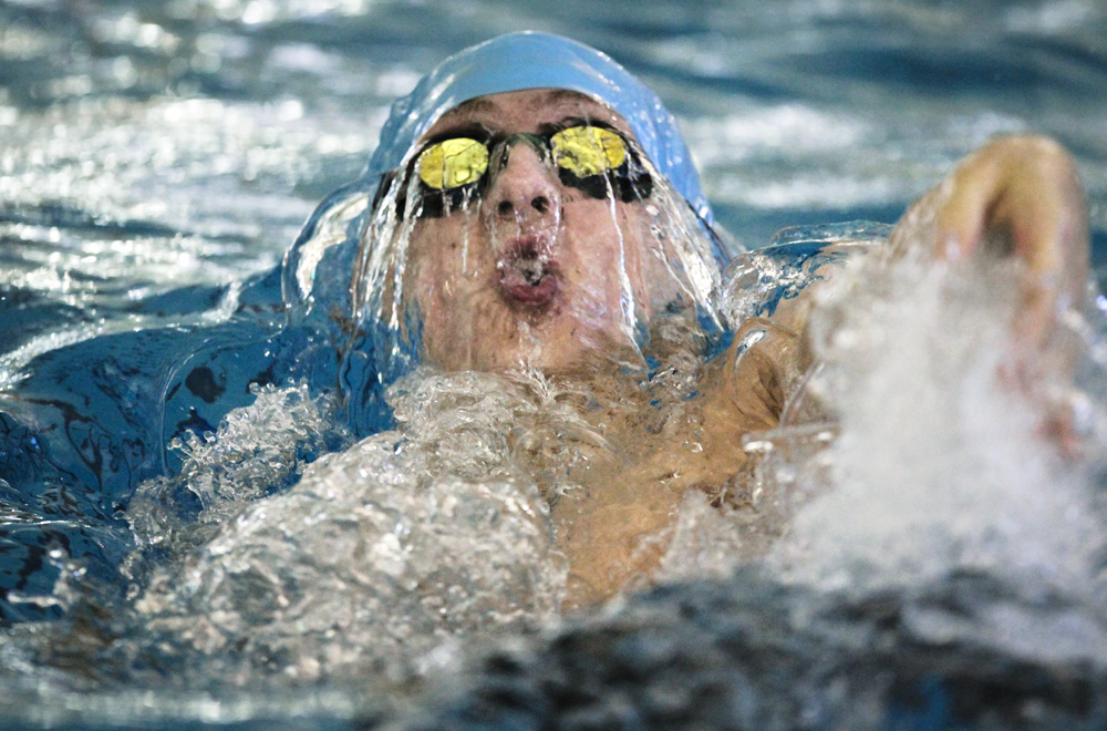 Troy DeMoss of Shawnee Mission East High School competes in the 100 yard backstroke.