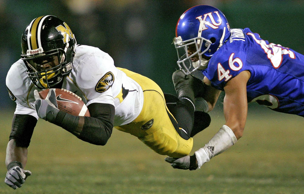 Missouri wide receiver Jeremy Maclin (left) is slowed down by Justin Thornton of Kansas.