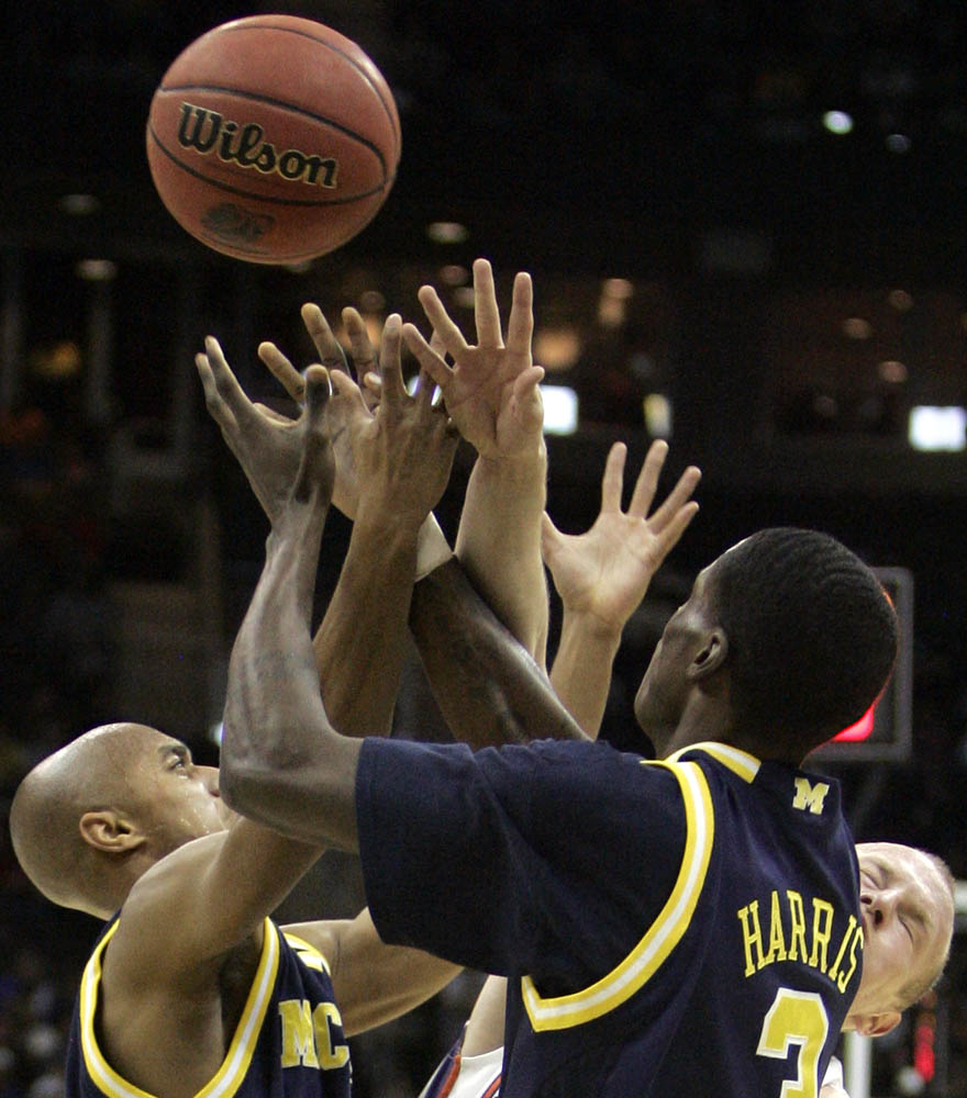Terrence Oglesby (right) of Clemson gets mugged by Michigan teammates C.J. Lee (left) and Manny Harris (right) during the mens NCAA Tournament.