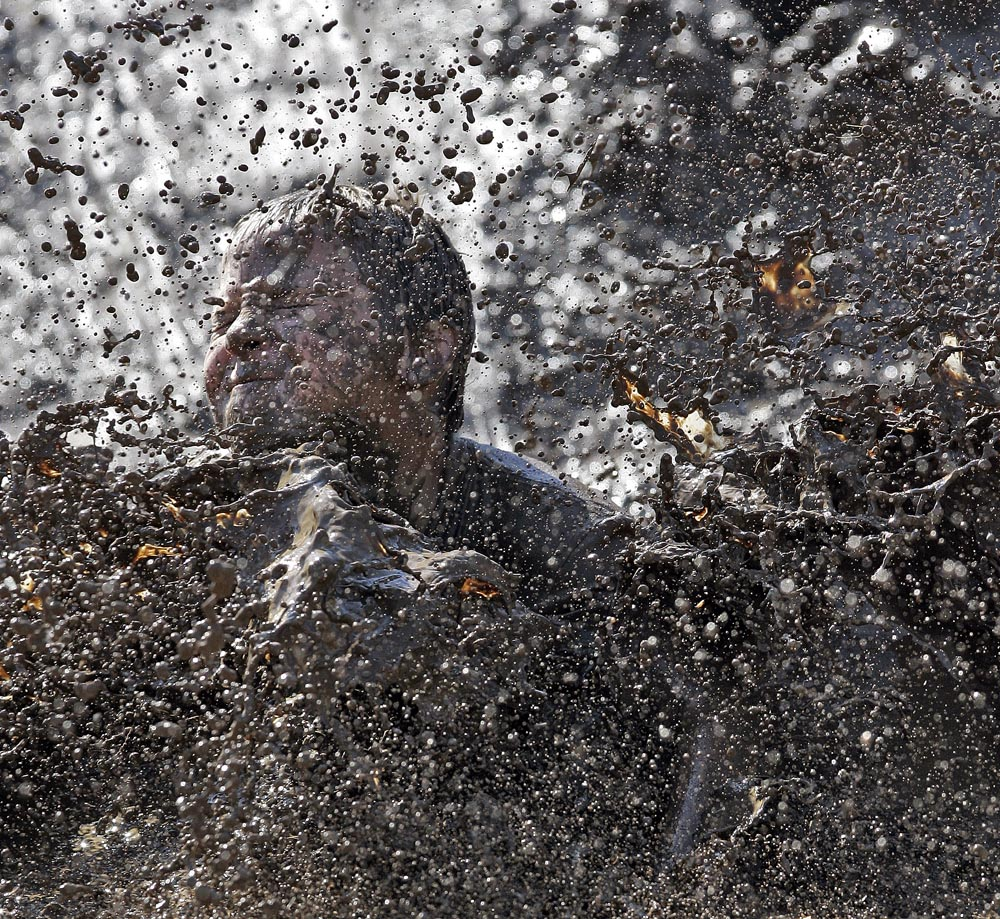 Eleven-year-old Cody Solomon of Grain Valley splashes down in a puddle of mud during a mud volleyball tournament.
