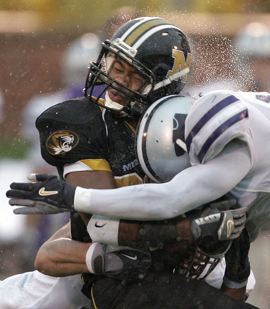 Missouri running back Tony Temple takes a shot from Byron Garvin of Kansas State during a rain soaked gameday.