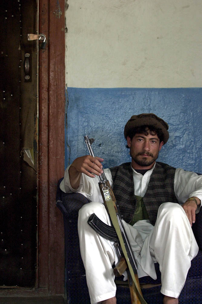 A soldier of Afghan warlord Mohammed Mustafa sits on guard for Mustafa from inside his compound in Khost, Afghanistan.
