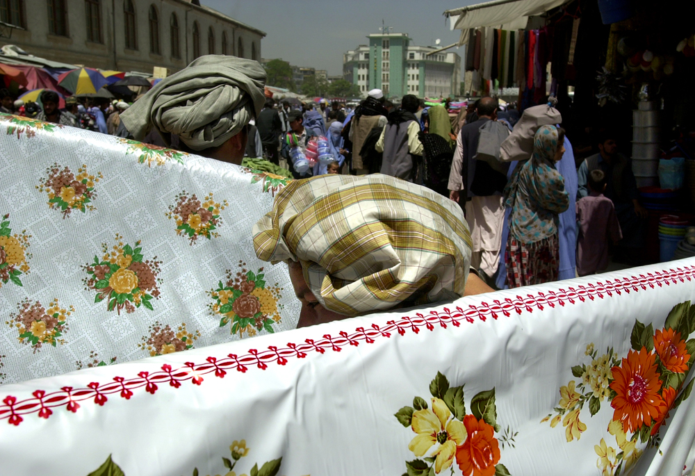 Two young boys exhibit their fabric to potential customers at the Mandai Street bizarre in Kabul, Afghanistan.