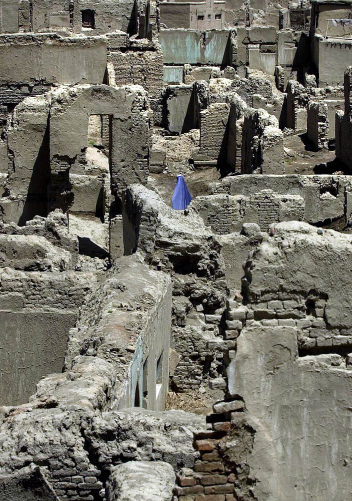 An Afghan woman bearing a burka walks through the bombed out village of Shorbazar, which is the old city of Kabul. Although the city is mostly unliveable, Afghans reside in the old village that was bombed as recently in 1998.